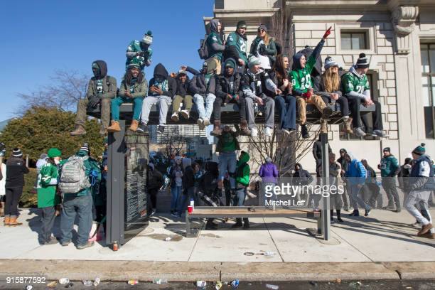 Philadelphia Eagles fans watch the Super Bowl LII parade from a bus stop waiting area on February 8 2018 in Philadelphia Pennsylvania