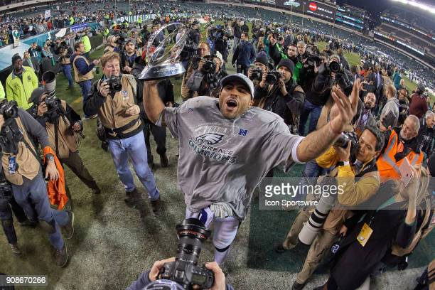 Philadelphia Eagles outside linebacker Mychal Kendricks celebrates with fans and teammates as he holds the George Halas Trophy after the NFC...