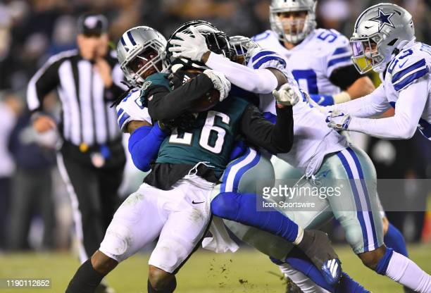 Philadelphia Eagles Running Back Miles Sanders is tackled by Dallas Cowboys Safety Xavier Woods and Dallas Cowboys Linebacker Jaylon Smith in the...