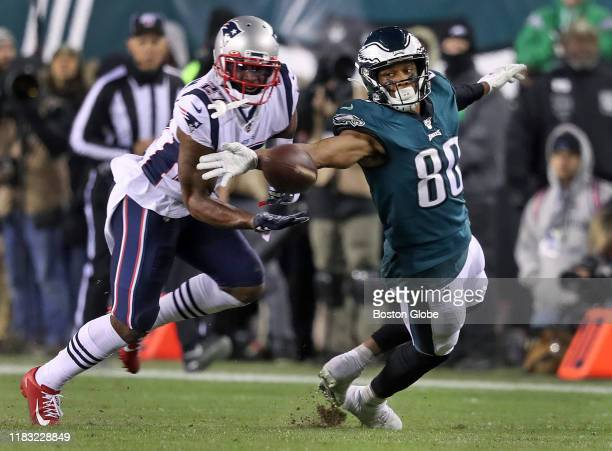 Philadelphia Eagles tight end Dallas Goedert reaches back and tips a ball thrown behind him preventing Patriots defensive back JC Jackson from making...