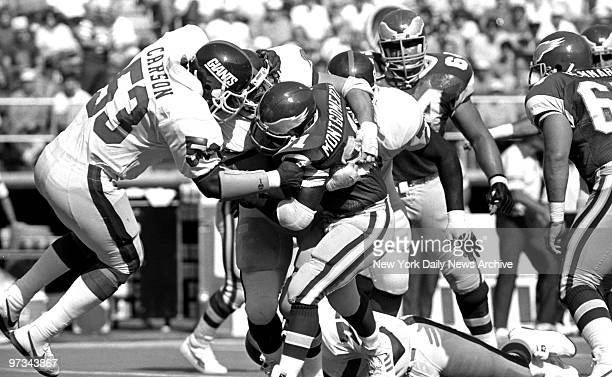 Philadelphia Eagles' Wilbert Montgomery is stopped by New York Giants defenders Harry Carson left and Jim Burt right during first quarter action in...