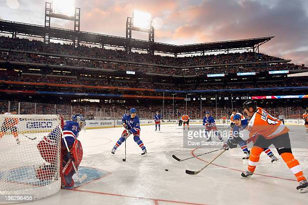 Philadelphia Flyers alumni John LeClair makes a pass across alumni Mark Messier of the New York Rangers as Dan Blackburn defends the net during the...