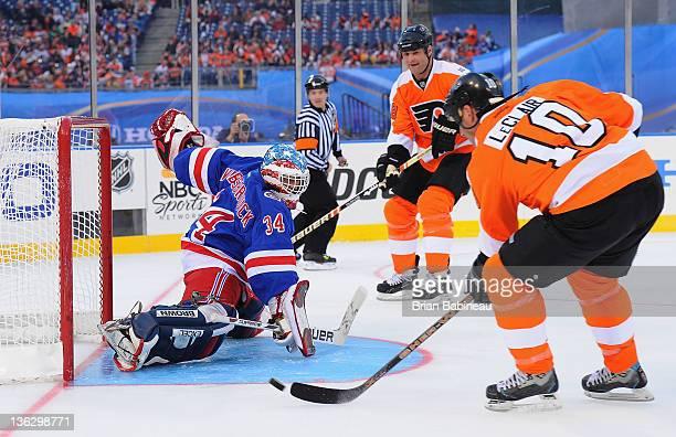 Philadelphia Flyers alumni John LeClair takes a shot on goaltender John Vanbiesbrouck during the Alumni game prior to the 2012 Bridgestone NHL Winter...