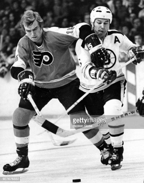 Philadelphia Flyers Bill Clement left and Boston Bruins Ted Green right battle for the puck during a game at the Boston Garden Dec 25 1971