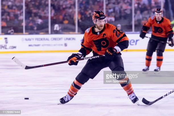 Philadelphia Flyers captain Claude Giroux makes a drop pass during the Stadium Series game between the Pittsburgh Penguins and the Philadelphia...