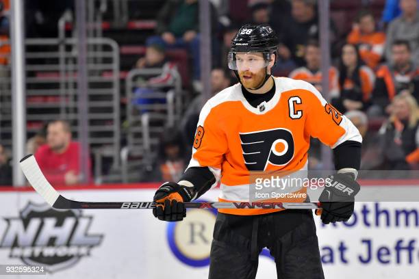 Philadelphia Flyers center Claude Giroux shows off his bloody face after taking a puck to the lip earlier in the game during the NHL game between the...