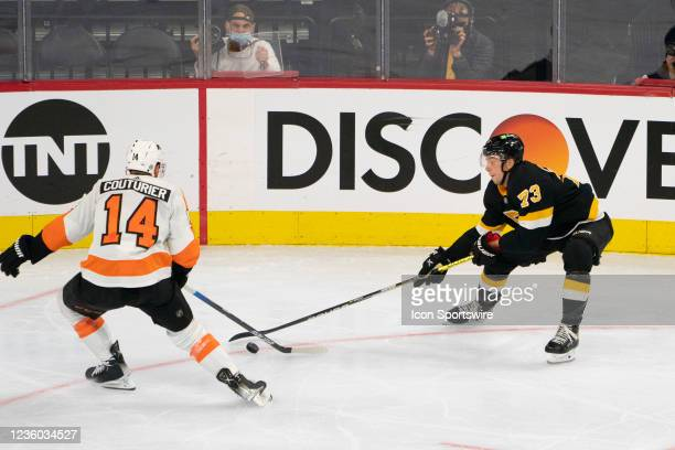 Philadelphia Flyers Center Sean Couturier and Boston Bruins Right Defenseman Charlie McAvoy battle for the puck during the second period of a...
