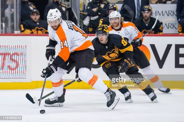 Philadelphia Flyers Center Sean Couturier skates with the puck ahead of Pittsburgh Penguins Center Sidney Crosby during the first period in the NHL...