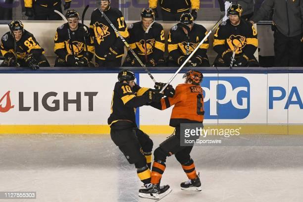Philadelphia Flyers Defenceman Travis Sanheim body checks Pittsburgh Penguins Right Wing Garrett Wilson during the Stadium Series game between the...