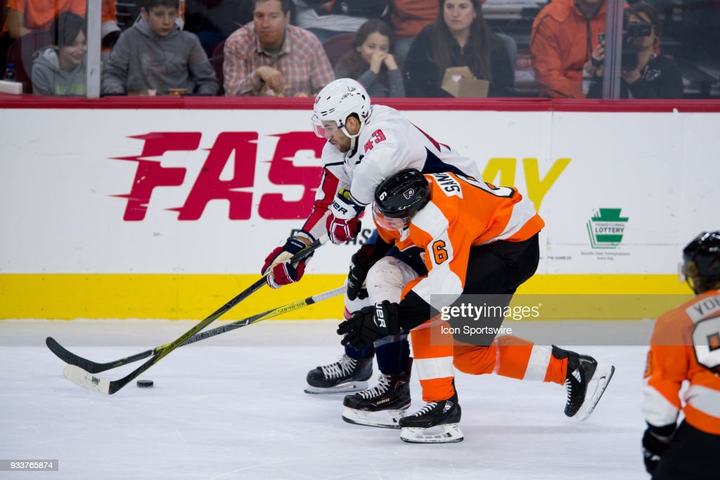 Philadelphia Flyers Defenceman Travis Sanheim (6) reaches in to take the puck from Washington Capitals Right Wing Tom Wilson (43) in the first period during the game between the Washington Capitals and Philadelphia Flyers on March 18, 2018 at Wells Fargo Center in Philadelphia, PA.