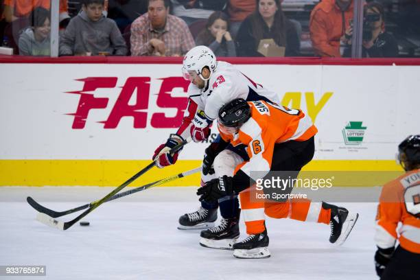 Philadelphia Flyers Defenceman Travis Sanheim reaches in to take the puck from Washington Capitals Right Wing Tom Wilson in the first period during...