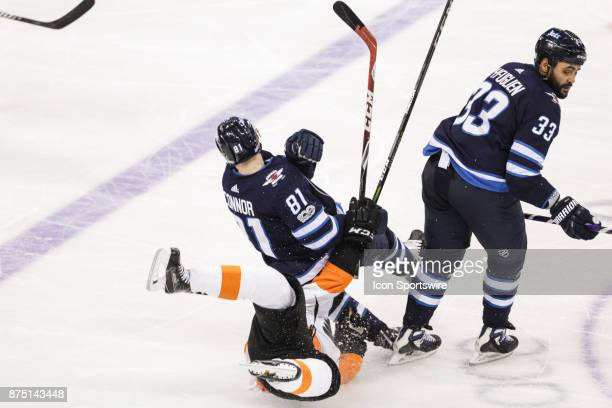 Philadelphia Flyers forward Jordan Weal falls to the ice after a body check by Winnipeg Jets defenseman Dustin Byfuglien during the NHL game between...