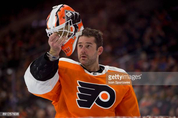 Philadelphia Flyers Goalie Brian Elliott inspects his helmet after being fallen on in the second period during the game between the Toronto Maple...