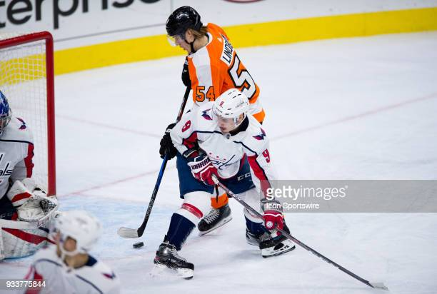 Philadelphia Flyers Left Wing Oskar Lindblom tries to shoot a loose puck into the net while being defended by Washington Capitals Defenceman Dmitry...