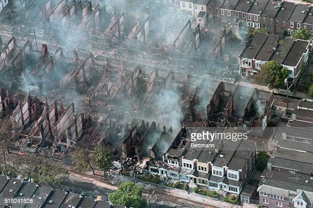 Aerial view of smoke rising from smouldering rubble where some 60 homes were destroyed by fire after a shoot out and bombing at the backtonature...