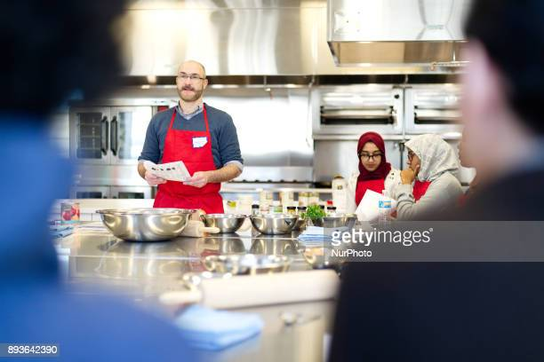 Philadelphia PA USA January 6 2016 A chef gives instructions as adult students and immigrants prepare food during an EnglishasaSecondLanguage course...