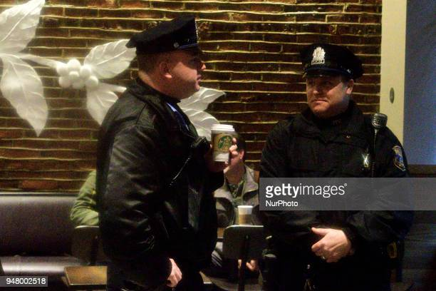 Philadelphia PD Police Officer holds a coffee cup as an estimated fifty protest at a Starbucks location in Center City Philadelphia PA USA on April...