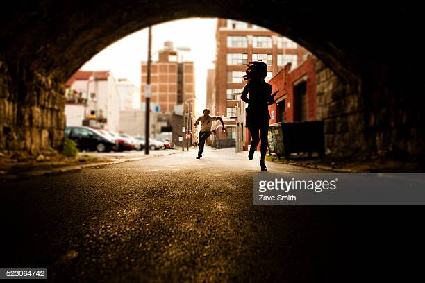 USA, Philadelphia, Pennsylvania, Woman being chased by criminal in urban underpass