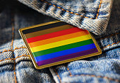 Philadelphia people of color inclusive flag pin on a denim jacket for LGBTQ identity, pride, and activism. The intersectional flag design is public domain for all uses.