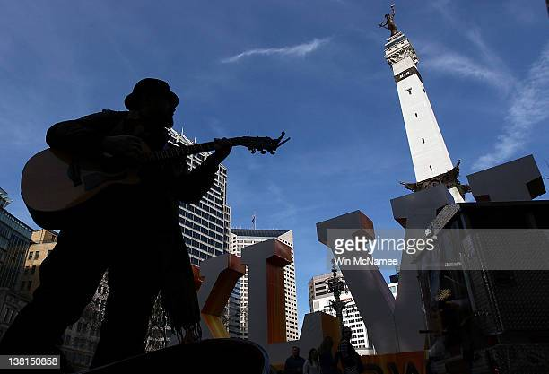 Philadelphia Phil plays his guitar for tips for fans visiting a giant Super Bowl XLVI logo at Monument Circle February 3 2012 in downtown...