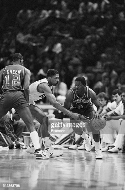 Philadelphia's Julius Erving grabs ahold of Detroit's Joe Dumars arm in an attempt to stop him from dribbling during second quarter of Philadelphia...