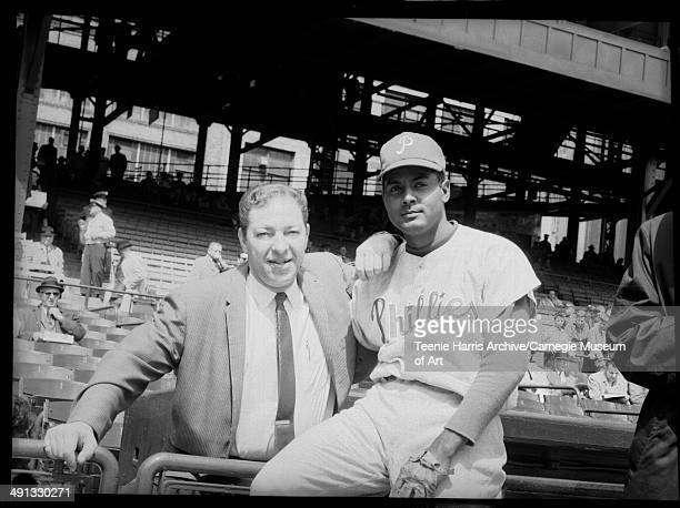 Philadelphia Phillies baseball player Ruben Amaro posing with a man in street clothes at Forbes Field Pittsburgh Pennsylvania circa 19601965