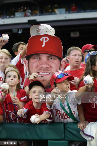 Philadelphia Phillies fans ask Bryce Harper to sign autographs before a game against the Los Angeles Dodgers at Citizens Bank Park on July 17, 2019...