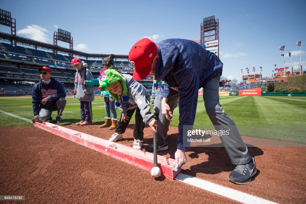 Philadelphia Phillies fans help the grounds crew lay the chalk in the outfield prior to the game against the Miami Marlins at Citizens Bank Park on April 8, 2018 in Philadelphia, Pennsylvania.