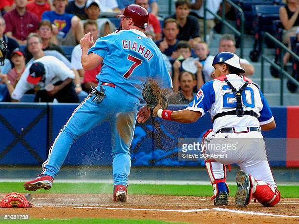 Philadelphia Phillies Jeremy Giambi scores on a second inning hit by Marlon Anderson as Atlanta Braves catcher Henry Blanco is late with the tag...