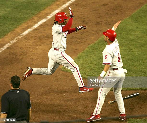 Philadelphia Phillies Jimmy Rollins high fives teammate Tomas Perez after scoring go ahead run a vs Los Angeles Dodgers Eric Gagne at Dodger Stadium