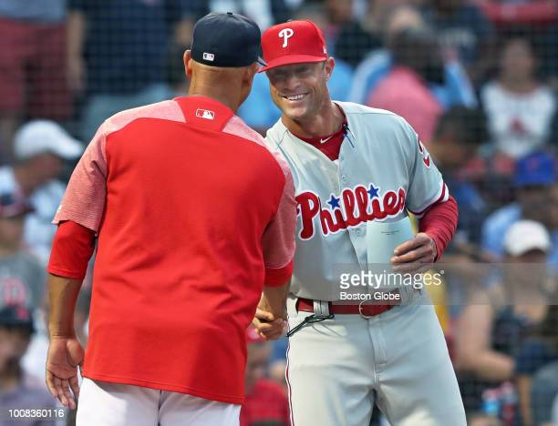 Philadelphia Phillies manager Gabe Kapler right smiles as he shakes hands with Red Sox manager Alex Cora as they meet at home plate before the game...