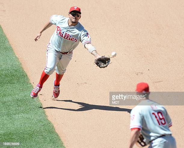 Philadelphia Phillies second baseman Freddy Galvis attempts to scoop the ball with his glove to Phillies first baseman Laynce Nix after he fielded a...