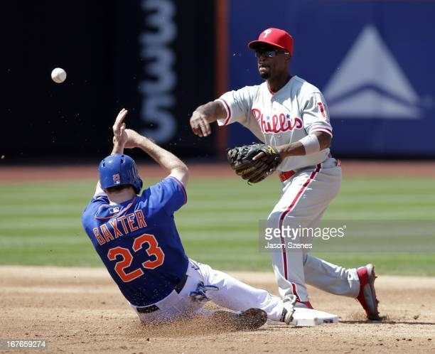 Philadelphia Phillies shortstop Jimmy Rollins turns a double play on New York Mets right fielder Mike Baxter in the third inning at Citi Field on...