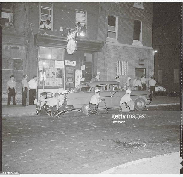 Police crouch behind a car as they are fired on by Negro rioters as the North Philadelphia disorders continue and grow into the second night
