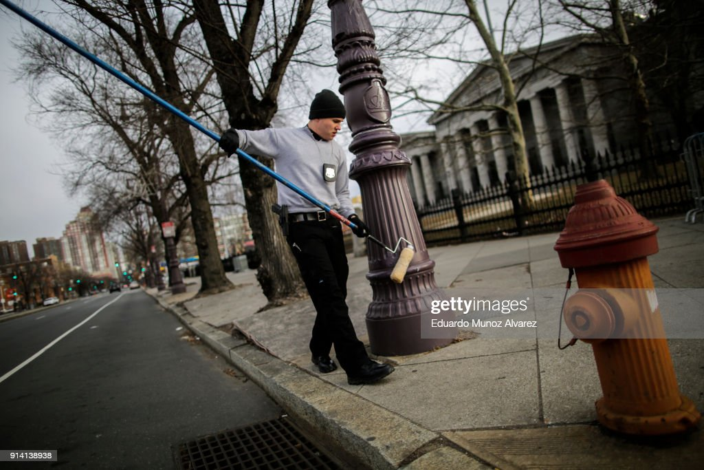 Philadelphia Police officer greases a traffic light pole as security measure for Super Bowl LII fans on February 4, 2018 in Philadelphia, Pennsylvania. The Philadelphia police department is using gear oil to grease up the poles on downtown streets to minimize the damage that fans can do to the city and themselves in the aftermath of the Super Bowl LII that will be played between the New England Patriots and the Philadelphia Eagles.