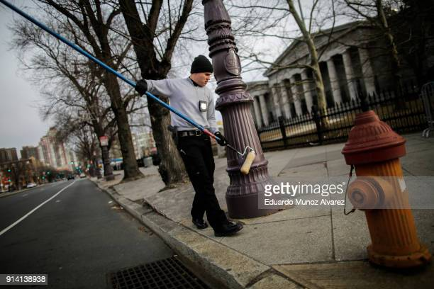 Philadelphia Police officer greases a traffic light pole as security measure for Super Bowl LII fans on February 4 2018 in Philadelphia Pennsylvania...