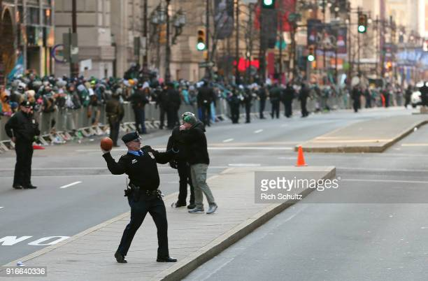Philadelphia Police officer loses a football to fanes lined up to watch the Eagles Super Bowl Victory Parade on February 8 2018 in Philadelphia...