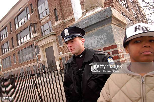 Philadelphia Police Officer Mik Olajewski stands watch as students are dismissed for the day at Pierce Elementary School a day after a boy and...