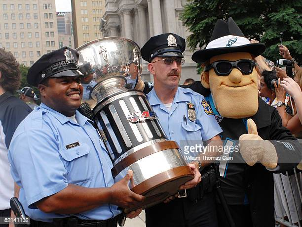 Philadelphia Police officers and the team mascot Soulman carry the Arena Bowl trophy during a championship parade at City Hall on July 27 2008 in...