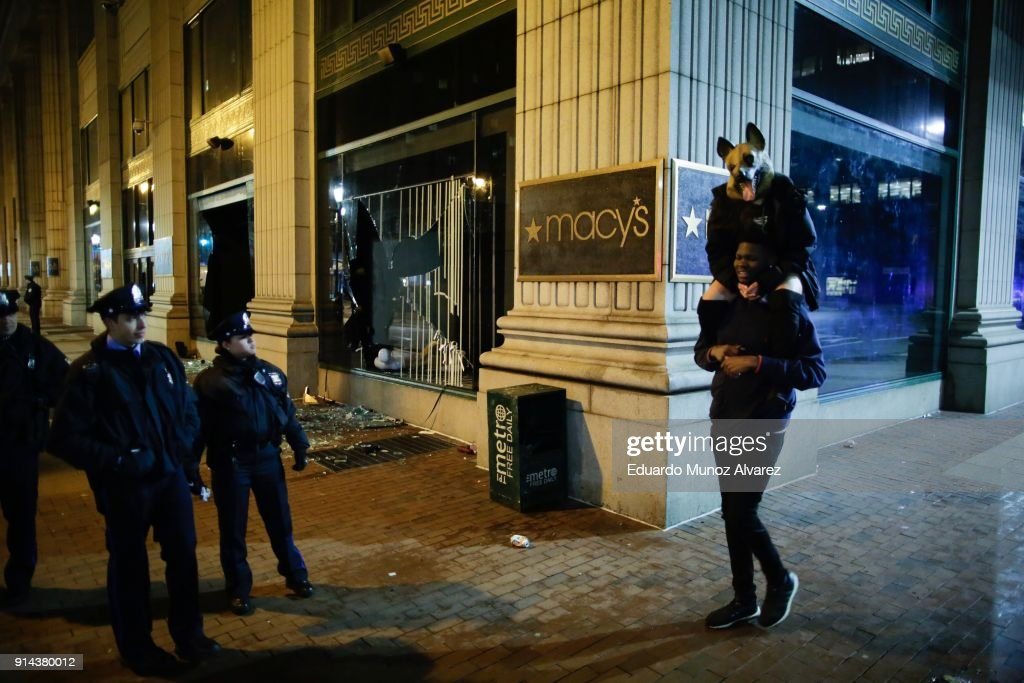 Philadelphia police officers try to keep fans away after broken macy's store windows while celebrating the Philadelphia Eagles' victory in Super Bowl LII game against the New England Patriots on February 5, 2018 in Philadelphia, Pennsylvania..