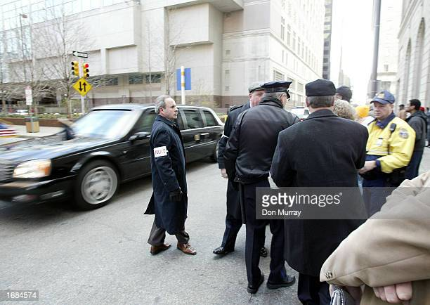 Philadelphia police stop an unidentified woman that started running up to US President George W Bush's car as the presidential car left the Marriot...