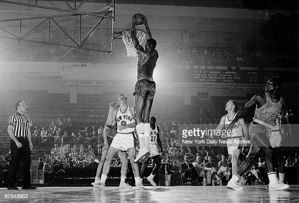 Philadelphia Warriors' Wilt Chamberlain stretches and dunks two points as baffled Phil Jordon and Johnny Green of the Knicks watch helplessly Wilt...