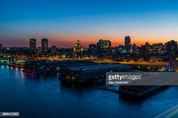 Philadelpia Downtown at sunset. The view from the Benjamin Franklin Bridge over the piers in Old City and Delaware River.