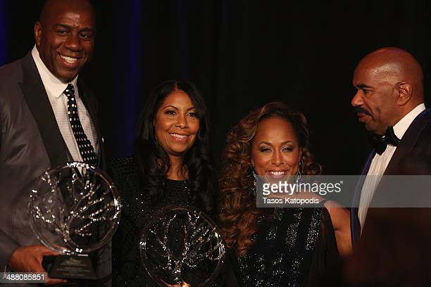 Philanthropists Cookie and Earvin 'Magic' Johnson accept an award onstage from Marjorie and Steve Harvey at the 2014 Steve Marjorie Harvey Foundation...