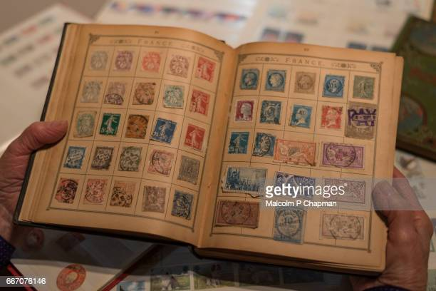 Philately - Senior woman looks at her postage stamp collection.