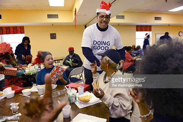 Philathropist Earl Stafford hands out holiday gifts to senior citizens Frenchie Lumpkin and Nancy Skinker at the Model Cities Senior Wellness Center...