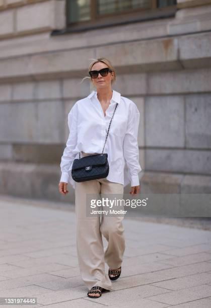 Philine wearing Soho Studios white blouse, black Chanel bag and beige Zara pants on July 30, 2021 in Hamburg, Germany.