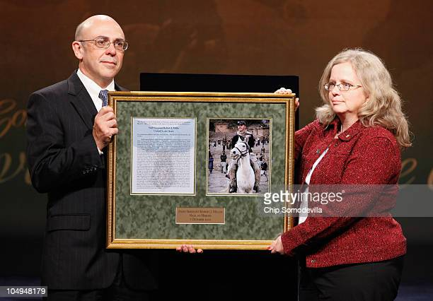 Philip and Maureen Miller the parents of Medal of Honor recipient US Army Staff Sgt Robert Miller hold a framed certificate and photograph of their...
