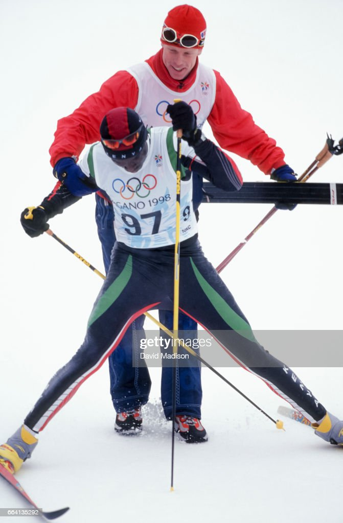 Philip Boit #97 of Kenya completes the Men's 10 Kilometer Classical event of the Nordic Skiing competition at the 1998 Winter Olympics held on February 12, 1998 at the Snow Harp venue in Hakuba near Nagano, Japan. Bjoern Daehlie of Norway, the Gold Medalist in the event, assists Boit after the finish.