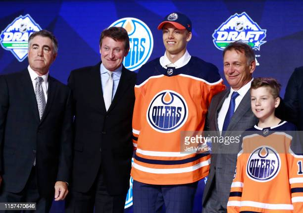 Philip Broberg eighth overall pick of the Edmonton Oilers poses for a group photo onstage with team personnel during the first round of the 2019 NHL...